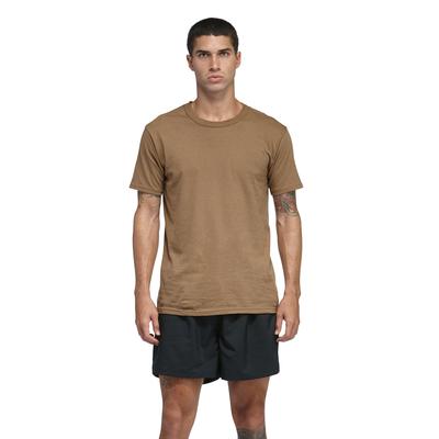 man facing front in a tan shortsleeve tshirt with black shorts