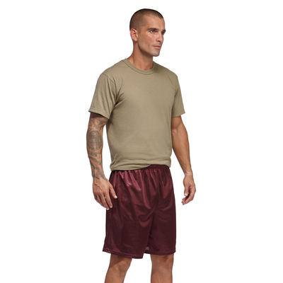 man standing at an angle in a tan shortsleeve tshirt and maroon mesh shorts
