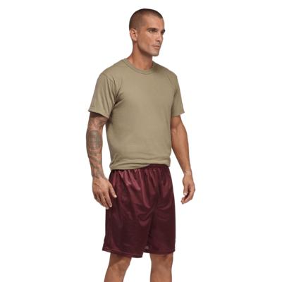 man standing at an angle in a tan shortsleeve tshirt and maroon mesh shorts