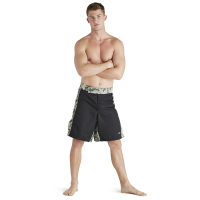 shirtless man standing with arms crossed wearing camo and black knee length training shorts