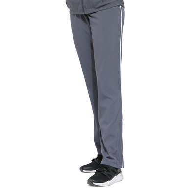 young womans legs angled forward wearing grey warmup pants and black running shoes
