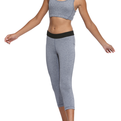 girl facing front wearing a match grey heather sports bra and capri leggings