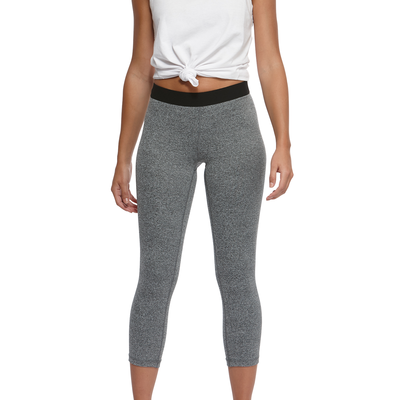 woman facing forward wearing a white knotted tank top and grey heather capri leggings