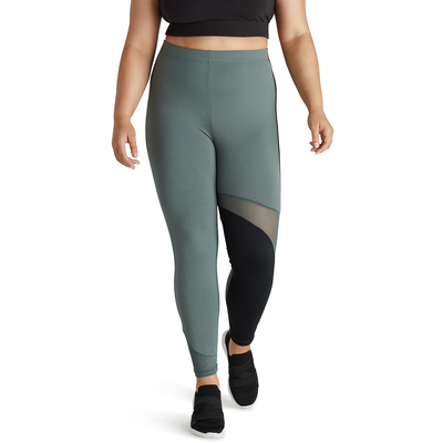 woman facing front wearing green leggings with black color blocking and mesh detail and black running shoes