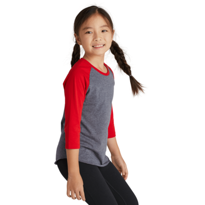 girl angled sideways wearing a grey and red baseball t shirt and black pants