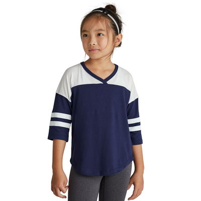 girl facing front wearing a navy blue and white striped v neck t shirt and grey pants