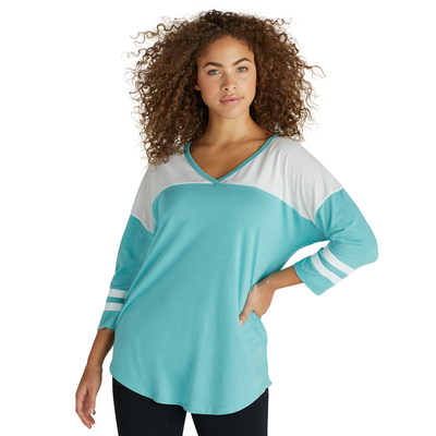 woman facing front wearing a turquoise and white striped v neck t shirt and black pants