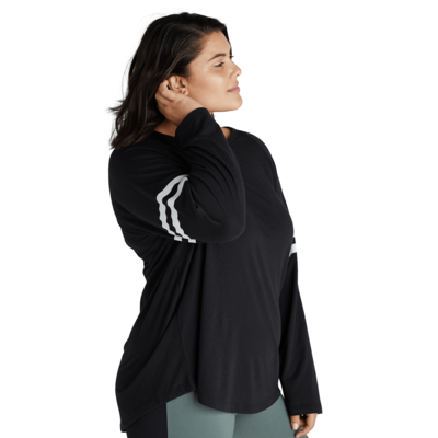 woman angled sideways wearing a black long sleeve t shirt with white stripes on the sleeves