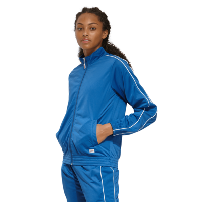 young woman angled front wearing a blue zip up warm up jacket and white piping on the sleeves