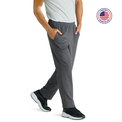 man angled sideways with hands in pockets wearing grey sweatpants