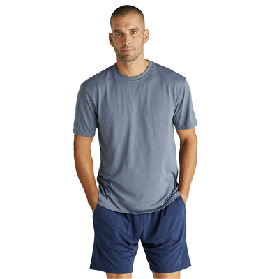 man facing front with hands in pockets wearing a grey short sleeve shirt and blue shorts