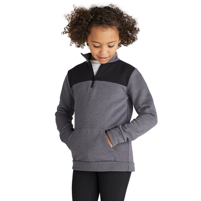 girl facing front looking down wearing a grey and black colorblocked quarter zip sweatshirt with hands in front pocket