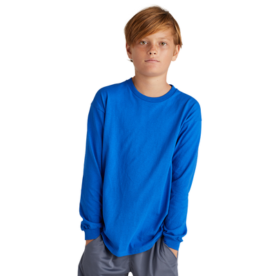 boy wearing a blue long sleeve shirt with both hands in shorts pockets