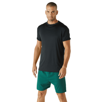 man angled sideways wearing a black short sleeve shirt and green jersey shorts