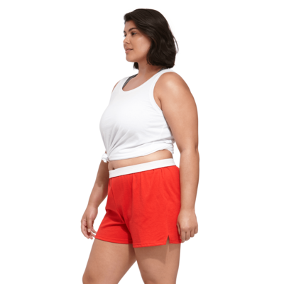 woman facing sideways wearing a knotted white tank top and red authentic soffe shorts