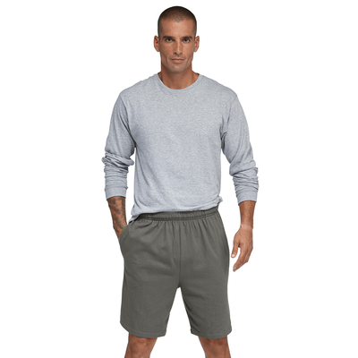 man facing front wearing a grey long sleeve shirt with grey jersey shorts and one hand in shorts pockets