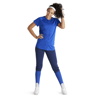 woman scrunching curly ponytail hand on hip wearing blue baseball pants and jersey
