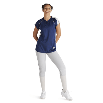 woman hands behind back pointing toe wearing white baseball pants and navy vee neck jersey