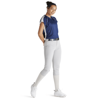 side view woman with hands behind back wearing white baseball pants and blue jersey