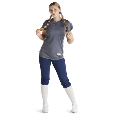 woman holding ends of pigtails wearing navy blue baseball pants and grey jersey