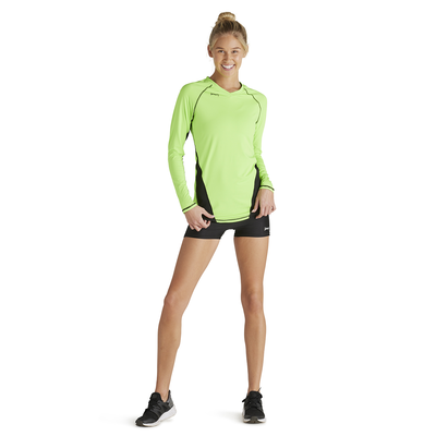 woman pulling down on bottom of long sleeve performance tee in lime green