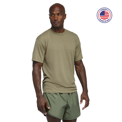 man looking sideways wearing a tan short sleeve shirt and green running shorts