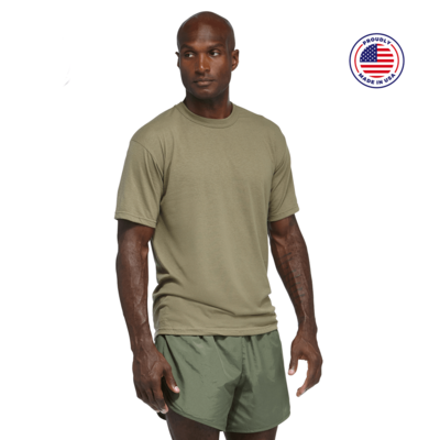man looking to the side wearing a tan short sleeve shirt and green running shorts
