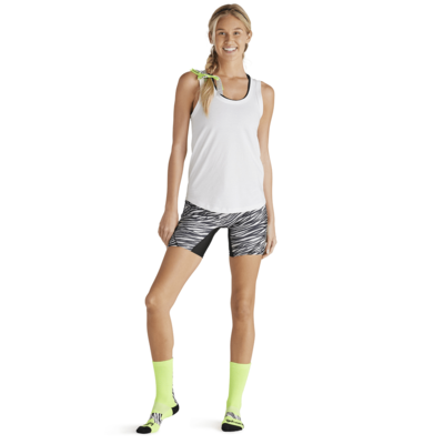 woman pointing toe wearing striped compression shorts and white tank top