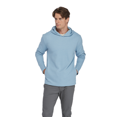 man looking to the left wearing a lt blue platinum hoodie with hand in side pockets